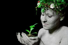 Mother earth. Holding plant sprout in her hands. Black background. studio shot royalty free stock photo