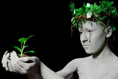 Mother earth. Holding plant sprout in her hands. Black background. studio shot royalty free stock images