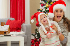 Mother and eat smeared baby in Christmas hats Royalty Free Stock Photos