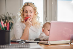 Mother eating apple at home office Stock Image