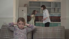 Mother and elder daughter arguing in the kitchen at home. Lillte girl covers her ears with hands. Problems in family stock video