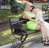 Mother embraced the son sitting on a bench Stock Images
