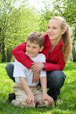 Mother embraces behind son sitting in lap on grass Stock Image