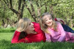 Mother embraces daughter lying on grass Stock Images