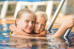 Mother embraces daughter near ladder in pool in tropical beach r Stock Photos