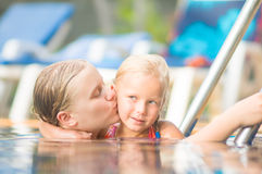 Mother embraces daughter near ladder in pool in tropical beach r Royalty Free Stock Photography
