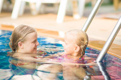 Mother embraces daughter near ladder in pool in tropical beach r Stock Image