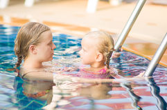Mother embraces daughter near ladder in pool in tropical beach r Stock Photo