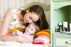 Mother embraces the sick child Stock Photos