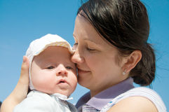 Mother embracing baby. Baby in mother's arms on blue sky background royalty free stock photos