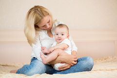 Mother embracing baby boy indoors Stock Images