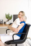 Mother embracing baby girl (21-24 months) in chair by desk in home office Stock Photos