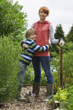 Mother Embracing Boy In Garden Stock Images