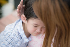 Mother embracing and consoling her son Stock Images