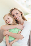 Mother embracing daughter on sofa Royalty Free Stock Photos