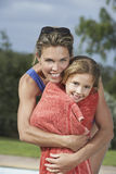 Mother Embracing Daughter Wrapped In Towel Stock Photography
