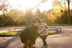 A mother embracing her baby girl in the park Stock Photos