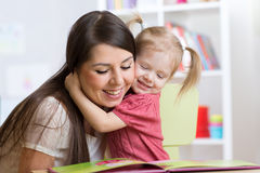 Mother  embracing and reading  a book to kid at home Stock Images
