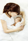 Mother embracing sleeping newborn baby stock images