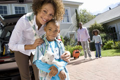 Mother embracing son (6-8) in driveway, father and daughter (8-10) in background, smiling, portrait stock photography