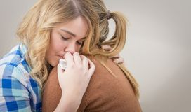 Mother embracing and soothes depressed daughter royalty free stock image