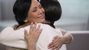 Mother embracing young daughter, empathy and tenderness, love and maternity. Stock footage stock footage