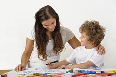 Mother encouraging child. Mother teaches her child how to draw Royalty Free Stock Photos