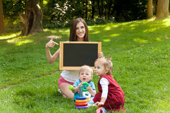 Mother engaged in the early development of children on nature in Royalty Free Stock Images