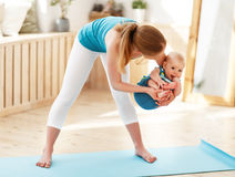 Mother is engaged in fitness with baby stock photos