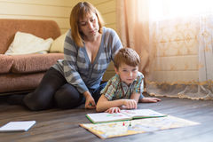 Mother is engaged in training young son. Royalty Free Stock Photography