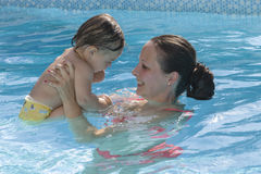 Mother enjoying a pool Stock Images