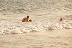 Mother enjoying sea waves, swimming with her children stock photography