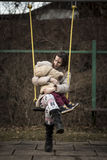 Mother enjoying on a swing in a park with her toddler in her lap Royalty Free Stock Image