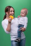 Mother entertaining toddler son with a toy fish Royalty Free Stock Photos