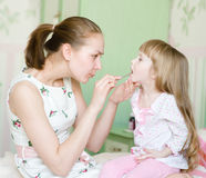 Mother examining little girl's throat Royalty Free Stock Image