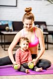 Mother exercising with her baby son at home. Portrait of a happy mother with her baby son exercising with dumbbells at home royalty free stock photo