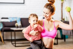 Mother exercising with her baby son at home. Portrait of a happy mother with her baby son exercising with dumbbells at home stock images