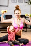 Mother exercising with her baby son at home. Portrait of a happy mother with her baby son exercising with dumbbells at home royalty free stock photos
