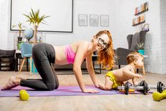 Mother exercising with her baby son at home. Young mother stretching on the mat with her baby son playing on the floor at home royalty free stock images