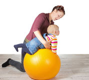 Mother exercising her young baby. Supporting it over a gym ball to stimulate muscle coordination and motion due to late development of motor skills Stock Image