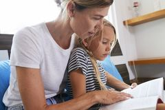Mother helping daughter with difficult task royalty free stock images