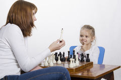 Mother explains daughter purpose of the chess pieces Stock Photos