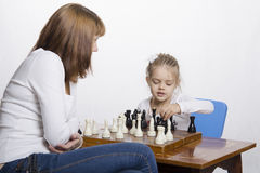 Mother explains daughter purpose of the chess pieces Royalty Free Stock Images