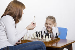 Mother explains daughter purpose of the chess pieces Royalty Free Stock Image
