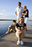 Mother and family, sunny day on dock by water. Mother enjoying sunny day on dock by water with family behind Royalty Free Stock Images