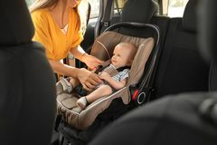 Mother fastening baby to child safety seat. Inside of car royalty free stock photo