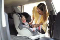 Mother fastening baby to child safety seat. Inside car stock photos