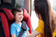 Mother fastening seat belt of son sitting in baby sit Stock Photos