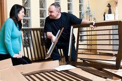 Mother and father assemble crib. Mother and father assemble a new baby bed (cot, crib) together royalty free stock images