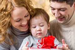 Mother, father and baby with christmas gift Stock Images